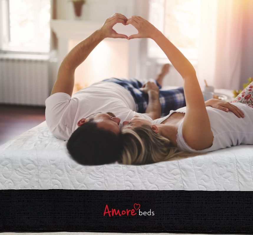 couple on bed with hands shaped like heart